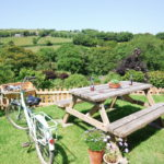 Picnic bench with beers and bike, view of vineyards